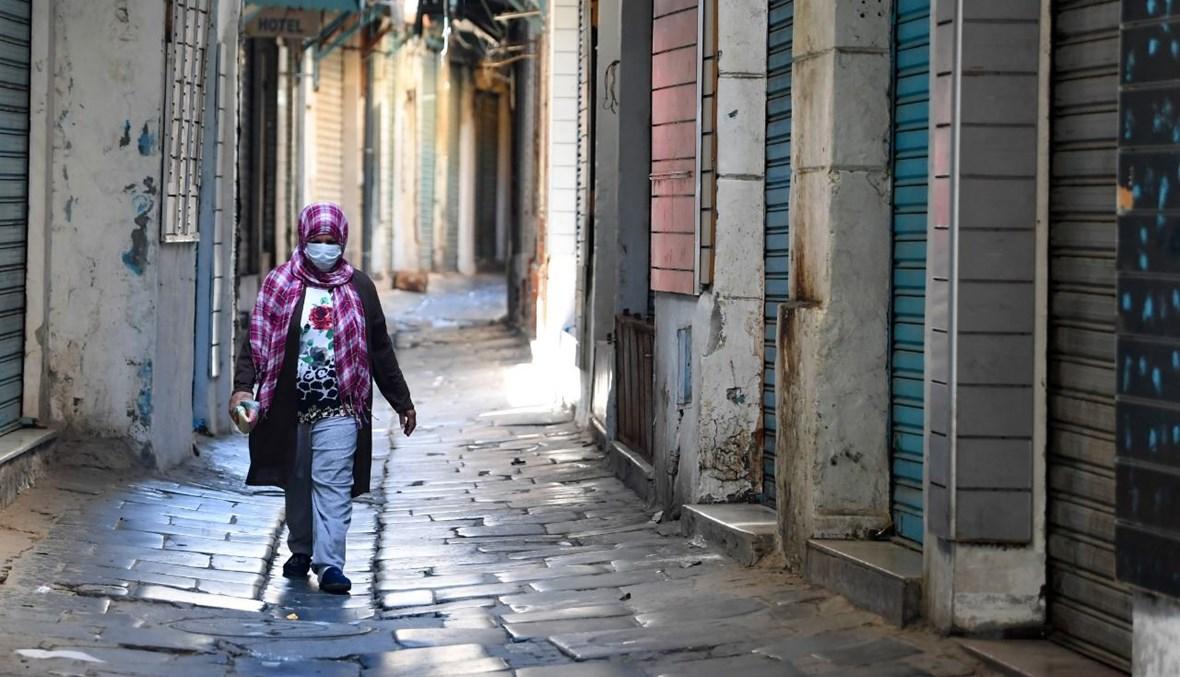 امرأة تمشي في سوق مغلقة في تونس (9 ايار 2021، أ ف ب).
