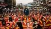 متظاهرون يحملون لافتات تظهر صورة الزعيمة المدنية الميانمارية المحتجزة أونغ سان سو كي يجلسون على طول أحد الشوارع قبل إقامة وقفة احتجاجية على ضوء الشموع خلال مظاهرة ضدّ الانقلاب العسكري في يانغون (أ ف ب).