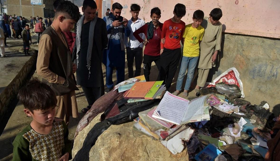 أطفال ينظرون الى حقائب مدرسية وكتب لضحايا تفجيرات استهدفت مدرسة للبنات في داشت إي بارشي في ضواحي كابول (9 ايار 2021، أ ف ب).