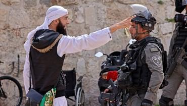 متظاهر فلسطيني يتجادل مع عنصر من قوات الأمن الإسرائيلية في البلدة القديمة بالقدس (10 ايار 2021، أ ف ب).