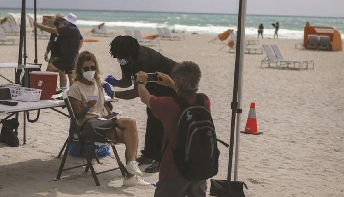 سياح من أميركا اللاتينية على شواطئ ميامي يتلقون اللقاح. (أ ف ب)