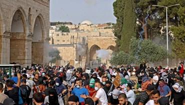 فلسطينيون يحاولون الإحتماء خلال المواجهات مع القوات الاسرائيلية في مجمع المسجد الأقصى بالقدس الشرقية أمس.(أ ف ب)