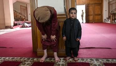 رجل وطفل يؤديان صلاة عيد الفطر في مسجد عبد الرحمن في كابول (13 ايار 2021، أ ف ب).