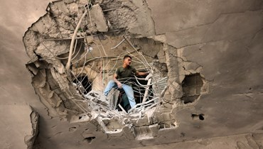 فلسطيني يتفقد الأضرار التي سببتها غارة جوية إسرائيلية على البنك الوطني الإسلامي التابع لحركة حماس في خان يونس جنوب قطاع غزة (13 ايار 2021، أ ف ب).