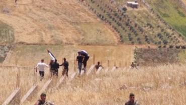 شبان يتخطّون السياج الحدودي.