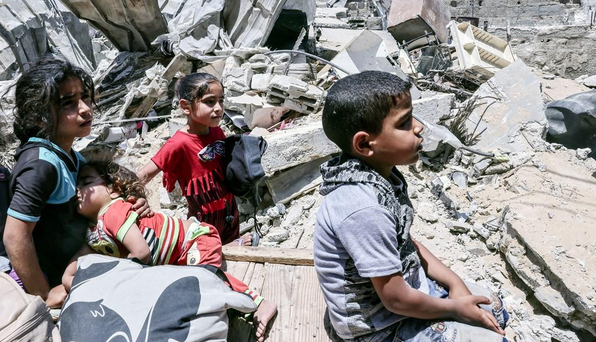 أطفال في غزّة يجلسون على أنقاض بيتهم المدمّر (أ ف ب).