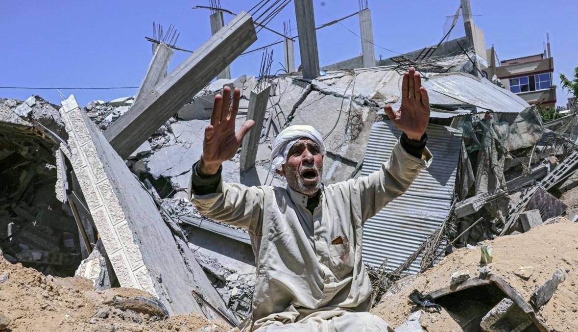 فلسطيني يجلس وسط أنقاض منزله بعدما دمرته غارة جوية إسرائيلية في مدينة رفح جنوب قطاع غزة (16 ايار 2021، ا ف ب).