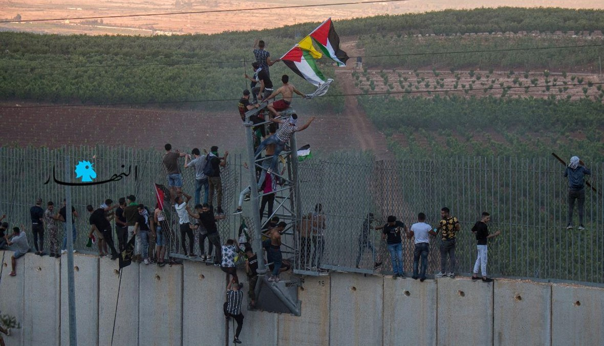 متظاهرون يتسلّقون جدا الإسمنت عند الحدود الجنوبية في كفركلا (نبيل اسماعيل).
