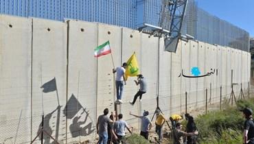 """متظاهرون يتسلّقون جدار الإسمنت الفاصل بين لبنان والحدود الفلسطينية في كفركلا لتثبيت علَمي """"حزب الله"""" وفلسطين (نبيل اسماعيل)."""