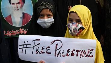 طفلتان تشاركان في تظاهرة في لاهور ضد الهجمات الإسرائيلية على قطاع غزة الفلسطيني (16 ايار 2021، أ ف ب).