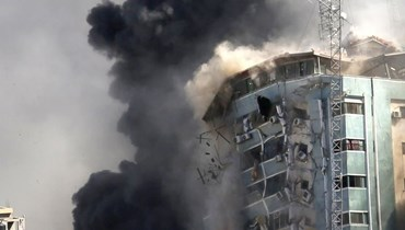"""البرج الضي يضم مكاتب وكالة """"الأسوشيتدبرس"""" الاميركية وقناة """"الجزيرة"""" الفضائية القطرية في مدينة غزة لحظة إنهياره من جراء الغارات الإسرائيلية السبت.   (أ ب)"""