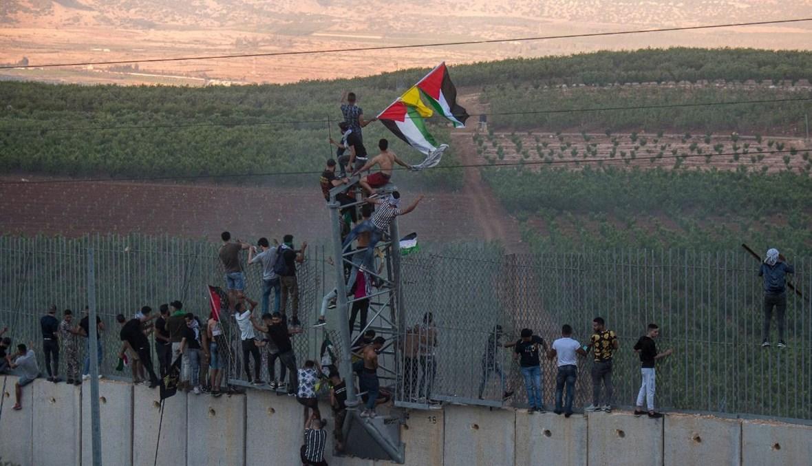 متظاهرون يتسلّقون جدار الإسمنت الفاصل عند الحدود الجنوبية في العديسة (نبيل اسماعيل).