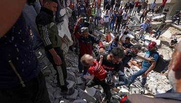 فلسطينيون ينتشلون جثة طفلة من تحت أنقاض مبنى دمرته غارة اسرائيلية في حي الرمال السكني بمدينة غزة أمس.   (أ ف ب)