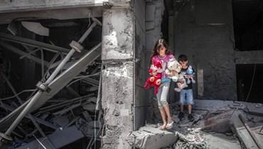 """طفلان فلسطينيان """"ينقذان"""" ألعابا من منزلهما في برج الجوهرة في مدينة غزة (17 ايار 2021، ا ف ب)."""