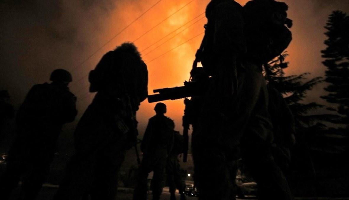 جنود إسرائيليون يقفون في حراسة بعد إطلاق قنابل ضوئية فوق بلدة المطلّة الشماليّة (أ ف ب).