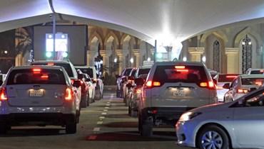 سعوديون بسياراتهم عند نقطة العبور إلى البحرين عبر جسر الملك فهد ليل الاحد. (أ ف ب)
