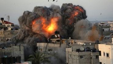 كتل من النار والدخان تتصاعد من مبانٍ استهدفها القصف الإسرائيلي في حي الرمال السكني بمدينة غزة ليل الأحد.   (أ ف ب)