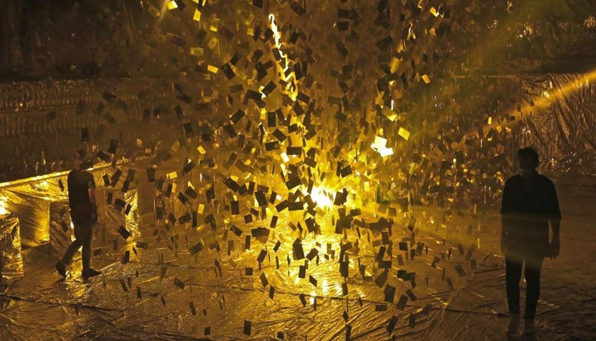 """أشخاص يزورون تركيبًا فنيًا بعنوان """"منهارة '' حول انخفاض قيمة الليرة اللبنانية للفنان اللبناني كارلو كسابان (أ ف ب)."""