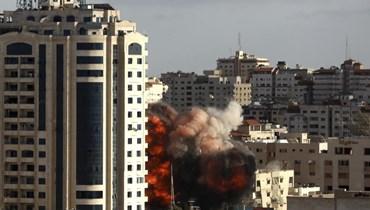 نار ودخان يتصاعدان من مبنى لدى تعرضة لغارة جوية إسرائيلية في مدينة غزة أمس.   (أ ب)