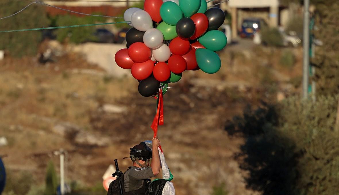عنصر من قوات الأمن الإسرائيلية يزيل بالونات نصبها فلسطينيون في حي الشيخ جراح بالقدس الشرقية (أ ف ب).
