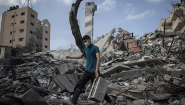فلسطيني فوق ركام مبنى من ستة طوابق دمرته غارة إسرائيلية في مدينة غزة أمس.(أ ب)