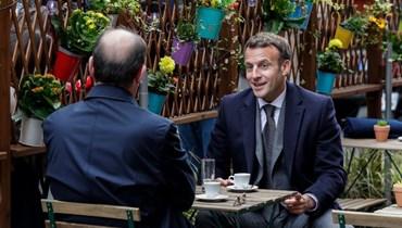 ماكرون ورئيس الوزراء الفرنسي يتناولان القهوة في مقهى بباريس (أ ف ب).