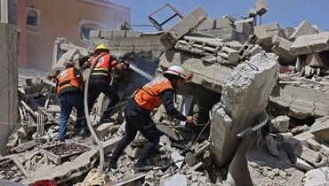 عمال إنقاذ فلسطينيون تجمعوا حول انقاض مبنى دمرته غارة جوية إسرائيلية على رفح جنوب قطاع غزة (20 ايار 2021، أ ف ب).