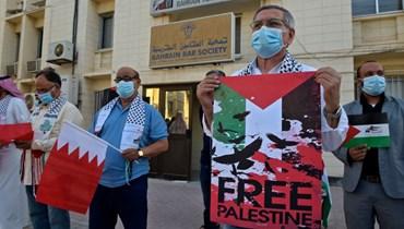 محامون بحرينيون يحملون لافتات خلال تجمع تضامني مع الفلسطينيين أمام مقر جمعية المحامين البحرينية في العاصمة المنامة (20 ايار 2021، أ ف ب).