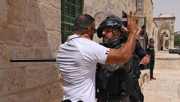 فلسطيني خلال مواجهة مع عنصر من القوات الامن الاسرائيلية في المسجد الأقصى بالقدس (21 ايار 2021، أ ف ب).