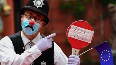 موظف في حديقة أوروبا في روست غرب ألمانيا يرتدي زي شرطي بريطاني لتذكير الزوار بالممارسات الصحية (21 ايار 2021، أ ف ب).