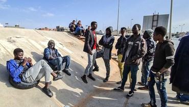 مهاجرون أفارقة ينتظرون تحت جسر في العاصمة الليبية طرابلس بحثاً عن عمل (6 آذار 2021، أ ف ب).
