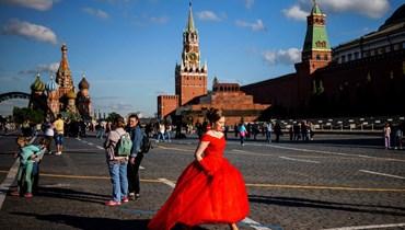 امرأة بفستان أحمر تمشي في الساحة الحمراء في موسكو (21 ايار 2021، أ ف ب).