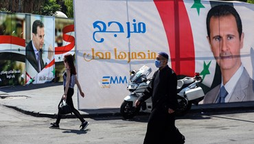 رفع صور للأسد في دمشق قبيل الانتخابات الرئاسية (أ ف ب).