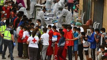 مهاجرون قاصرون ينتظرون اخضاعهم لفحص كورونا لدى وصولهم إلى جيب سبتة الإسبانية (19 ايار 2021، أ ف ب).