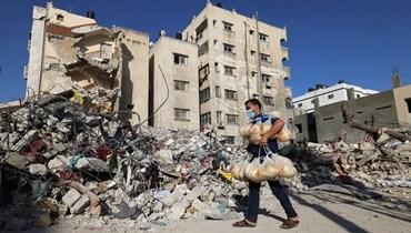 عامل فلسطيني يمر بالقرب من أنقاض مبنى دمرته الغارات الاسرائيلية في مدينة غزة (27 ايار 2021، أ ف ب).