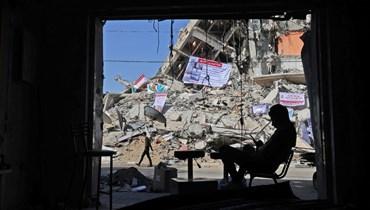 رجل يجلس في متجر متضرر في مبنى مدمر جزئيا من جراء الغارات الجوية الإسرائيلية الأخيرة في مدينة غزة (26 ايار 2021، ا ف ب).