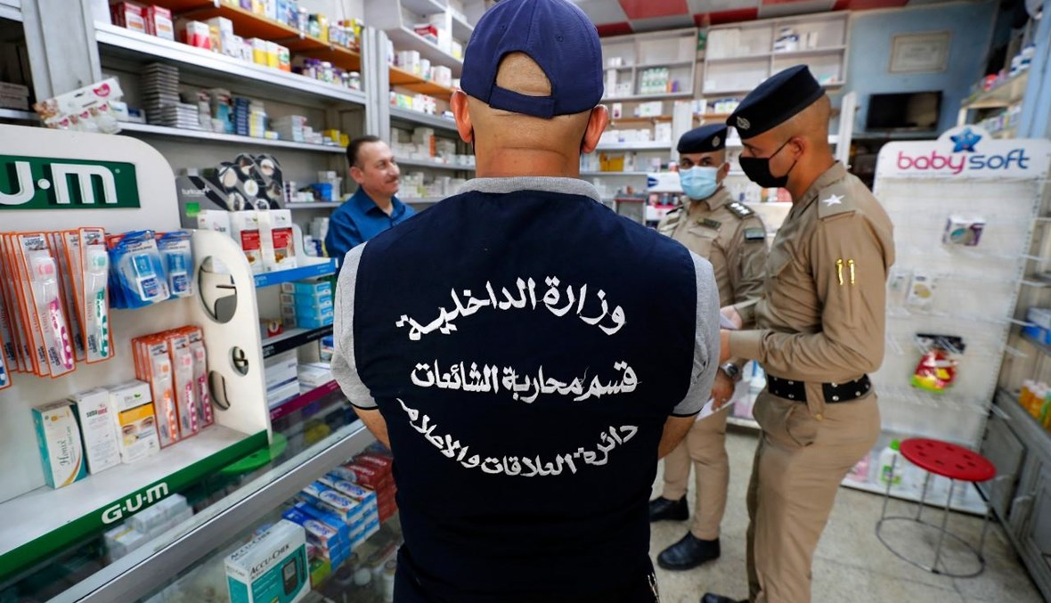 """عنصر من فريق مكافحة """"الأخبار الكاذبة"""" في وزارة الداخلية العراقية ورجال شرطة، خلال حديثهم الى صيدلاني في العاصمة بغداد، في إطار حملة لنشر الوعي حول الأخبار الكاذبة (20 ايار 2021، أ ف ب)."""