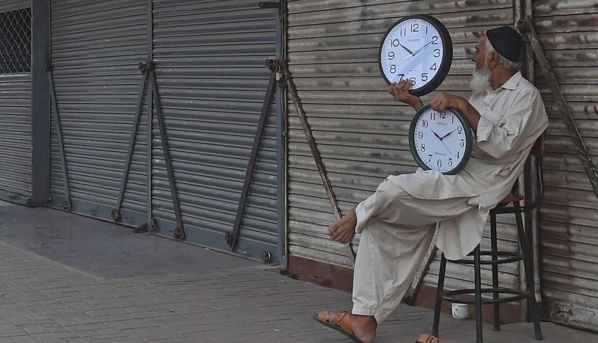 بائع متجول يحمل ساعات حائط لبيعها في كراتشي (28 ايار 2021، أ ف ب).