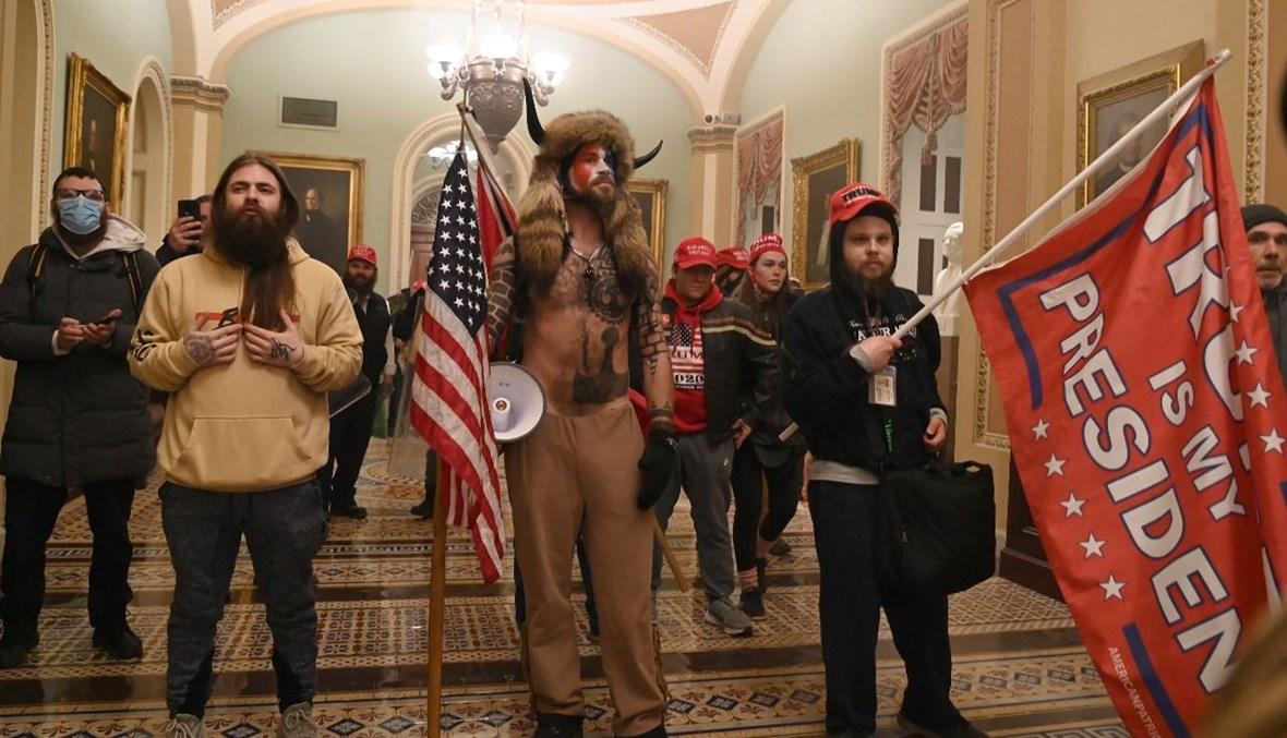 """أنصار لترامب، بينهم عضو مجموعة """"كيو أنون"""" جيك أنجيلي، خلال اقتحامهم مبنى الكابيتول في واشنطن (6 ك2 2021، أ ف ب)."""