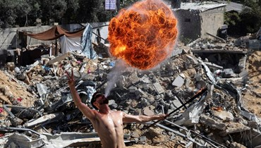 """شاب فلسطيني من فريق """"بار وولف"""" الرياضي يقدّم عرضاً بالنار فوق أنقاض مبنى دمرته الضربات الجوية الإسرائيلية في بيت لاهيا (أ ف ب)."""