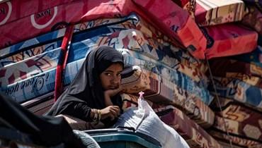 فتاة سورية تجلس في شاحنة بعد إطلاقها من مخيم الهول في شمال شرق محافظة الحسكة السورية (2 حزيران 2021، ا ف ب).