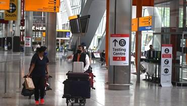 مسافرون يدفعون أمتعتهم في مطار هيثرو بلندن (3 حزيران 2021، ا ف ب).