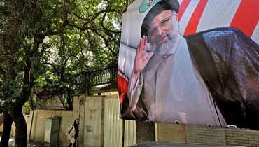 شخص يمر بالقرب من ملصق انتخابي لرئيس القضاء المرشح الرئاسي إبراهيم رئيسي في طهران (1 حزيران 2021، أ ف ب).