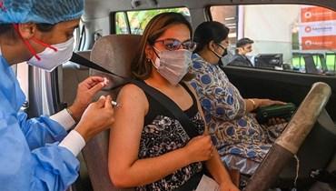 ممرضة تلقح امرأة ضد كورونا خلال حملة تلقيح بالسيارات في نيودلهي أمس.   (أ ف ب)