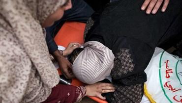 والدة الطفل الفلسطيني عبيدة الدحدوح تعانق جسده وهي تبكي مع أقاربه خلال تشييعه في مدينة غزة (10 حزيران 2021، أ ف ب).