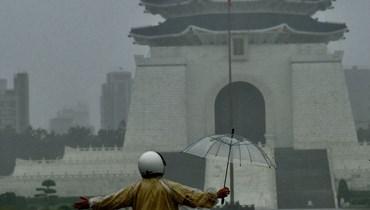 رجل يقف تحت أمطار غزيرة أمام قاعة تشيانغ كاي شيك التذكارية في تايبيه (4 حزيران 2021، أ ف ب).