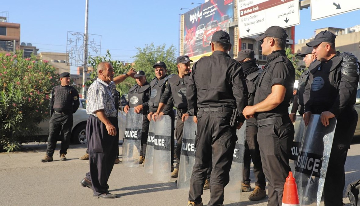 عناصر من الشرطة العراقية يقفلون طريقًا، بينما يتظاهر أكراد العراق في مدينة السليمانية احتجاجًا على الهجوم التركي في شمال العراق (5 حزيران 2021، أ ف ب).