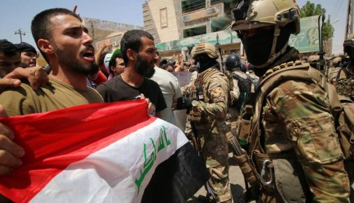 صورة لشابّ يرفع العلم العراقي