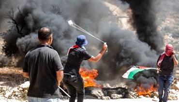 فلسطينيون خلال مواجهات مع قوات الأمن الإسرائيلية في قرية بيتا جنوب نابلس في الضفة الغربية المحتلة (11 حزيران 2021، ا ف ب).