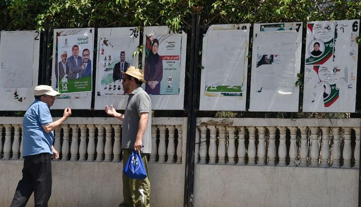 رجلان يتحدثان في الطريق في العاصمة الجزائر (11 حزيران 2021، ا ف ب).